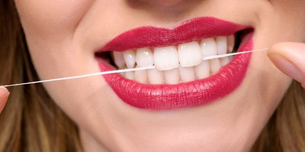 young woman teeth with dental floss.