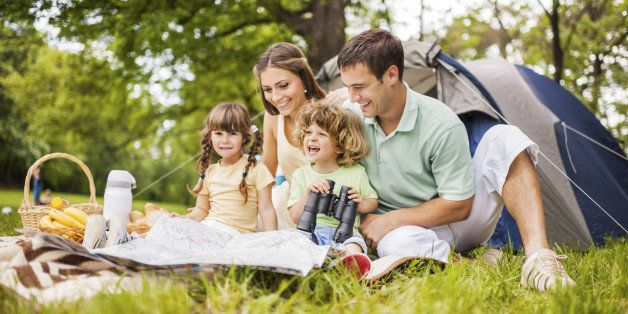 Young parents with their little children enjoying in family camping.