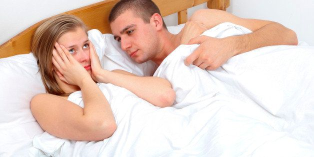 Young couple lying in bed having sexual issues.