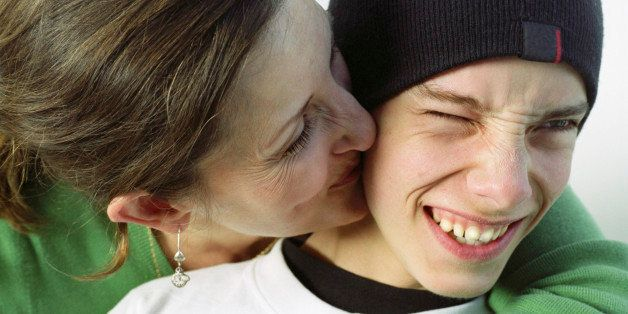 Mother kissing teenage boy (14-16) on cheek, close-up