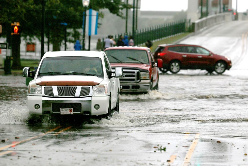 Cars go through a flooded street during the heavy rain of outer bands of Hurricane Florence in New Bern on Thursday.
