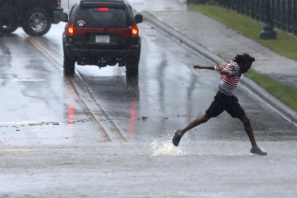 A pedestrian crosses the street during the heavy rain of outer bands of Hurricane Florence in New Bern on Thursday.