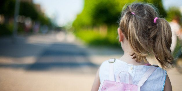 Toddler girl with backpack going to school with two ponytails
