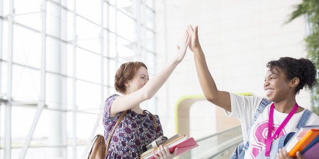University students high fiving indoors