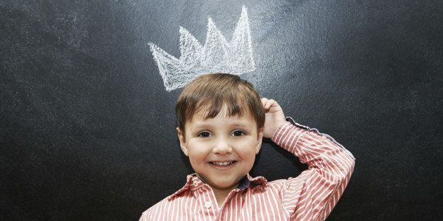Studio shot of an adorable little boy with a drawing of a crown on a blackboard behind him