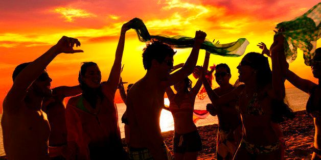 Tropical beach party. Spring break backlit image of a group of more than ten teenagers or young women and men dancing at sunset on a tropical beach. People wearing swimsuits and dancing on the sand of a tropical Caribbean island beach in Morrocoy, Venezuela. Image taken at sunset during short vacations with people in the foreground and the sea and sun in the background, Predominant color: yellow. Backlit DSLR outdor photo taken with a Canon 5D Mk III.