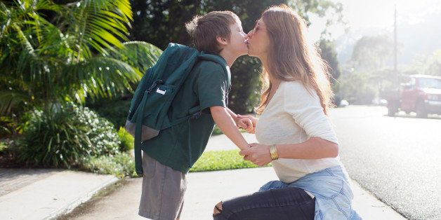 Boy kissing mother goodbye walking to school