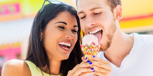 Hispanic couple sharing ice cream cone outdoors