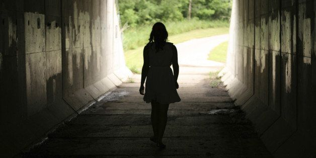 A young woman moving out of darkness into light.