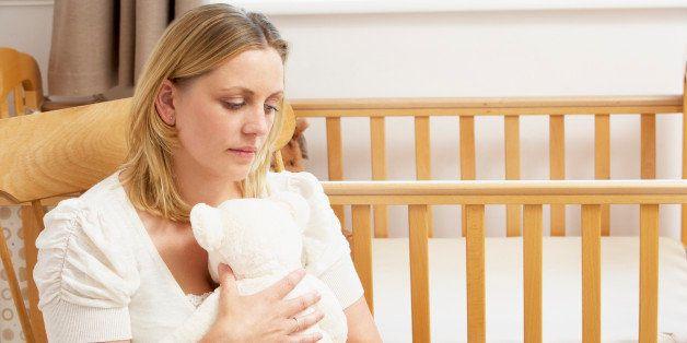 Sad Mother Sitting In Empty Nursery