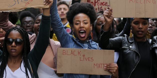 TOPSHOT - Demonstrators from the Black Lives Matter movement march through central London on July 10, 2016, during a demonstration against the killing of black men by police in the US. 