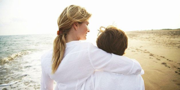Mother and son (8-10) walking on beach, rear view, close-up