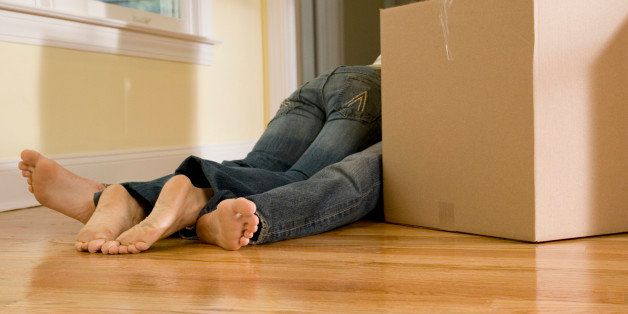 Woman laying on man behind moving boxes