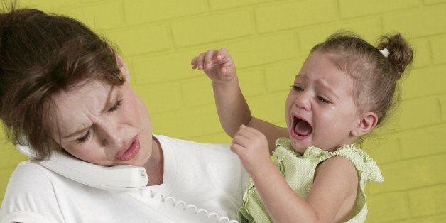 Pregnant woman holding crying girl while talking on telephone