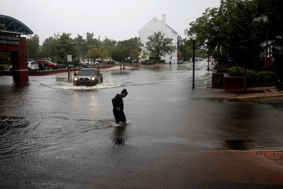 A man tries to cross the street during the heavy rain of outer bands of Hurricane Florence in New Bern,...