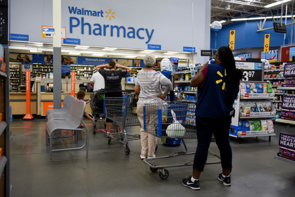 Shoppers wait in line to be served at the pharmacy of a Walmart Inc. store ahead of Hurricane Florence...