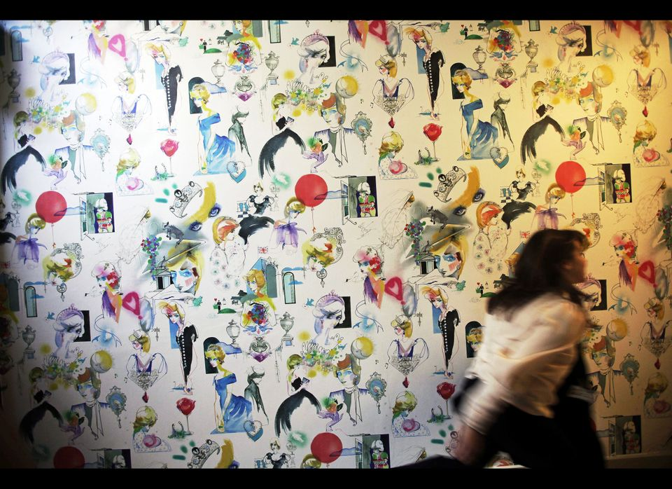 A woman walks past wallpaper bearing different drawings of the late Princess Diana during a press preview visit at what used
