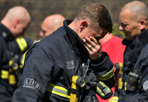 A firefighter looks at the floral tributes left by the Latymer Community Centre before a minute's silence...