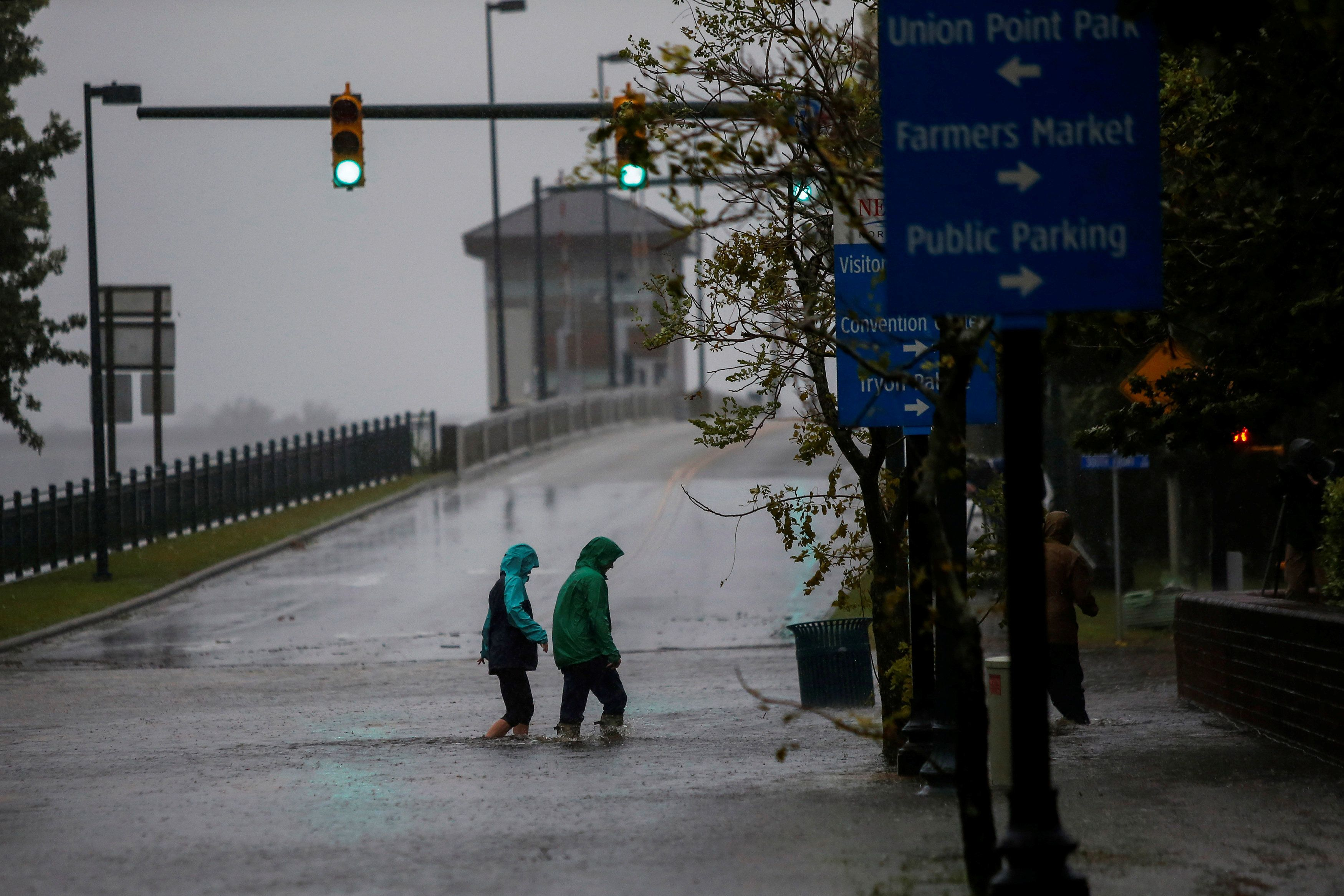 People walk on a local street as water from Neuse River starts flooding houses upon Hurricane Florence coming ashore in New Bern, North Carolina, U.S., September 13, 2018. REUTERS/Eduardo Munoz