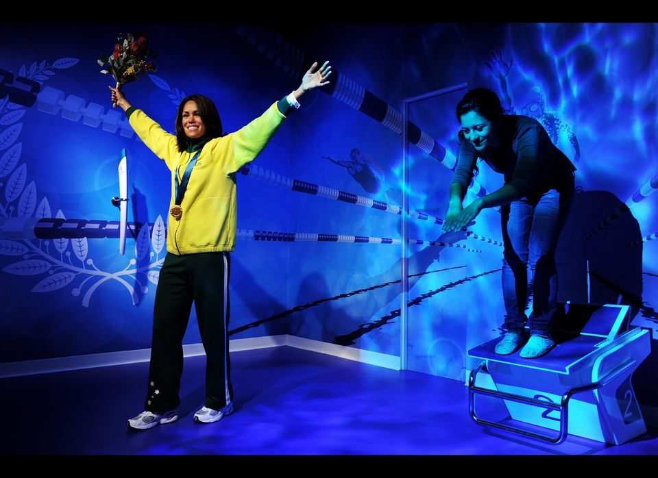 A visitor (R) poses on a swimming start block alongside a wax figure of Australia's former Olympic sprinter Cathy Freeman (L)