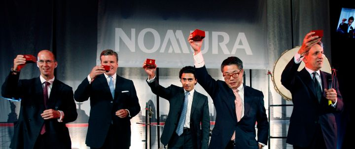 Executives from Japanese bank Nomura celebrate the completion of their acquisition of Lehman Brothers' European operation in