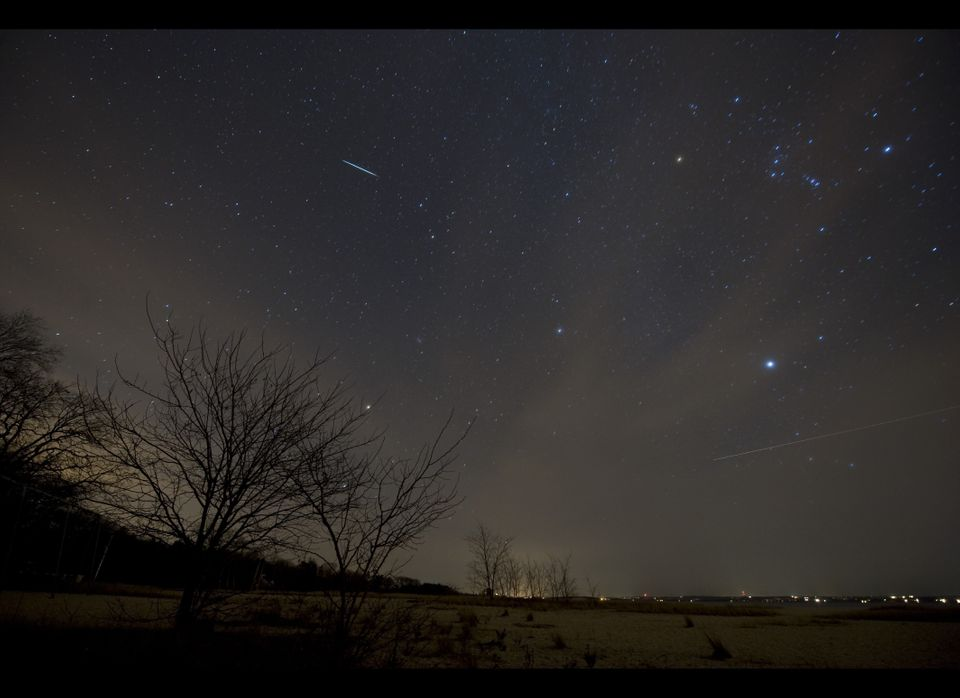 A meteor from the Geminids meteor shower (streak at top) enters the Earth's atmosphere on December 12, 2009 above Southold, N