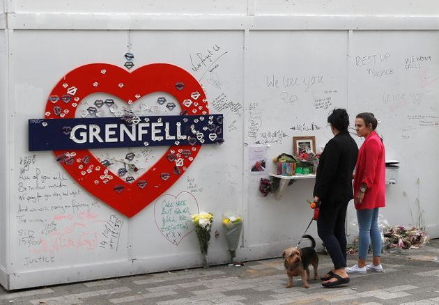 Women look at a hoarding covered in messages of condolence at the base of Grenfell tower one year after...