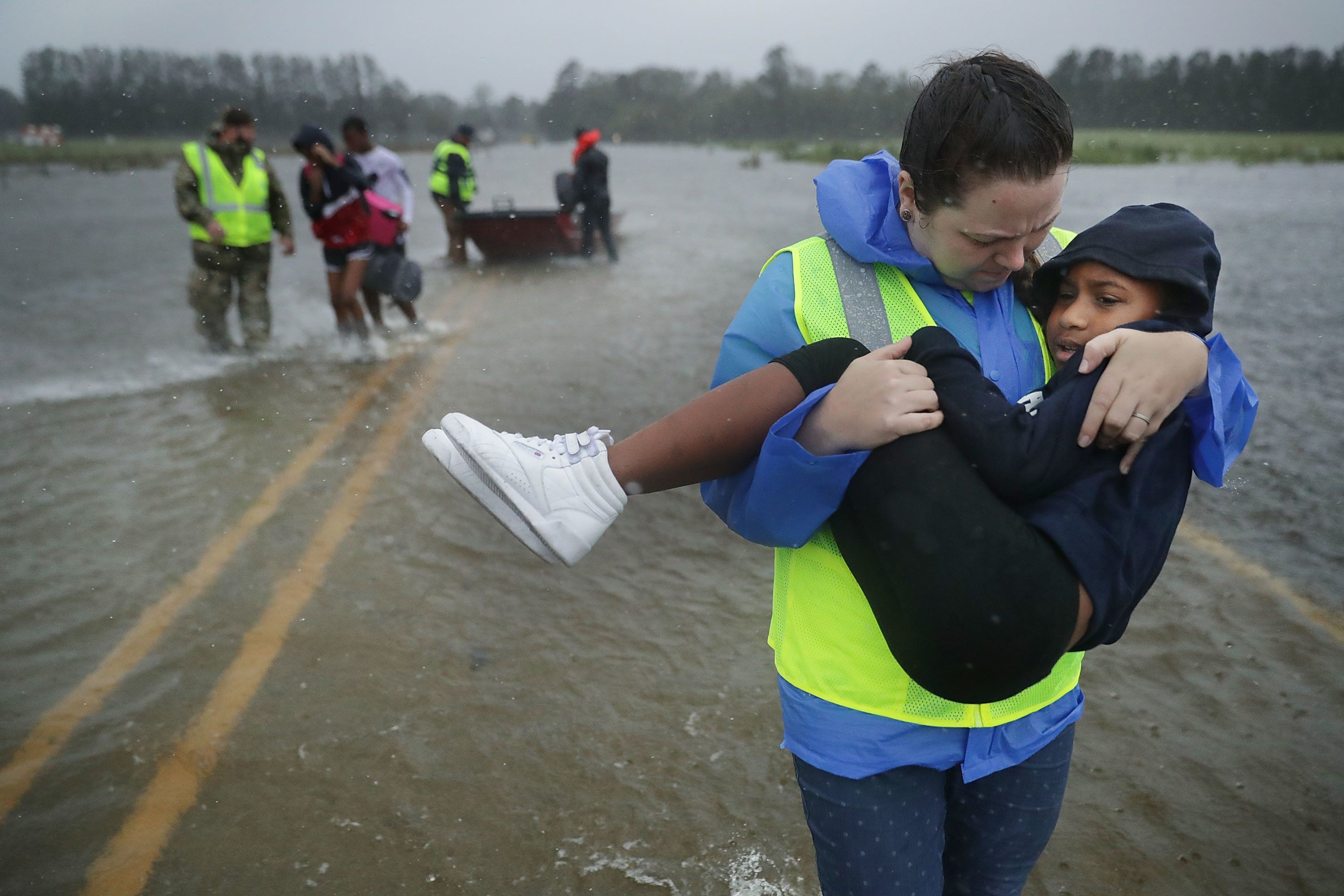 JAMES CITY, NC - SEPTEMBER 14:  Volunteers from the Civilian Crisis Response Team help rescue three children from their flooded home September 14, 2018 in James City, United States. Hurricane Florence made landfall in North Carolina as a Category 1 storm and flooding from the heavy rain is forcing hundreds of people to call for emergency rescues in the area around New Bern, North Carolina, which sits at the confluence of the Nueces and Trent rivers.  (Photo by Chip Somodevilla/Getty Images)