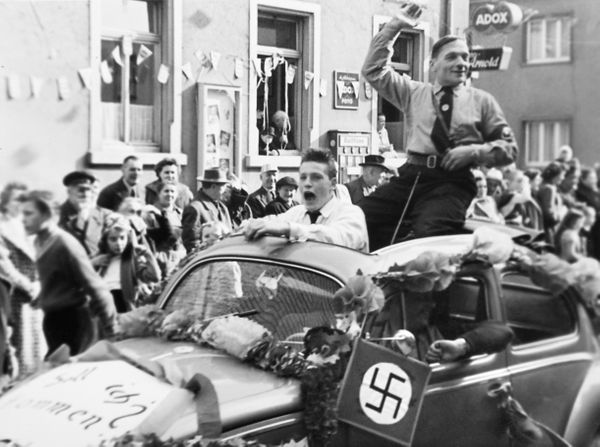 <i>A Nazi Party member rides in the back of a Volkswagen during a parade in Germany circa 1935.</i>