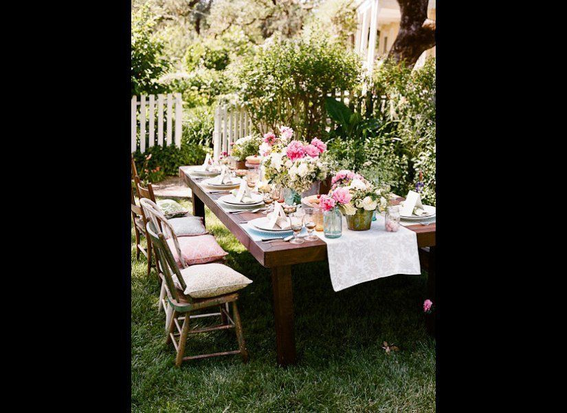 """Dress up a basic farm table with bunches of brightly-colored flowers in mismatched mason jars and vases.  Photo by <a href="""""""
