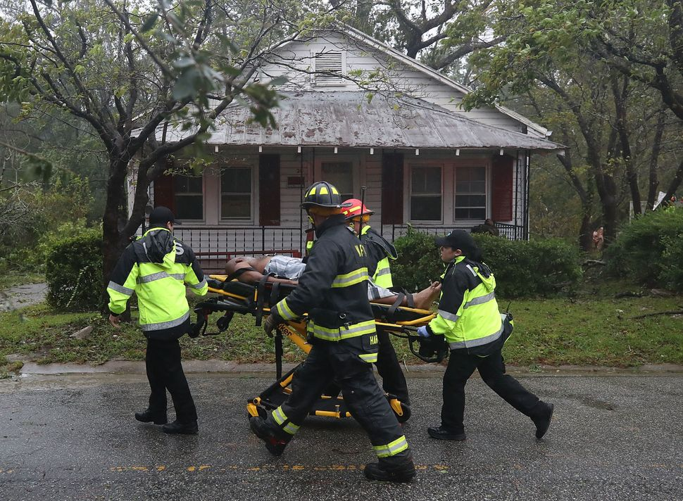 Rescue personnel remove a man from a home that a large tree fell on that had three people trapped after Hurricane Florence hi