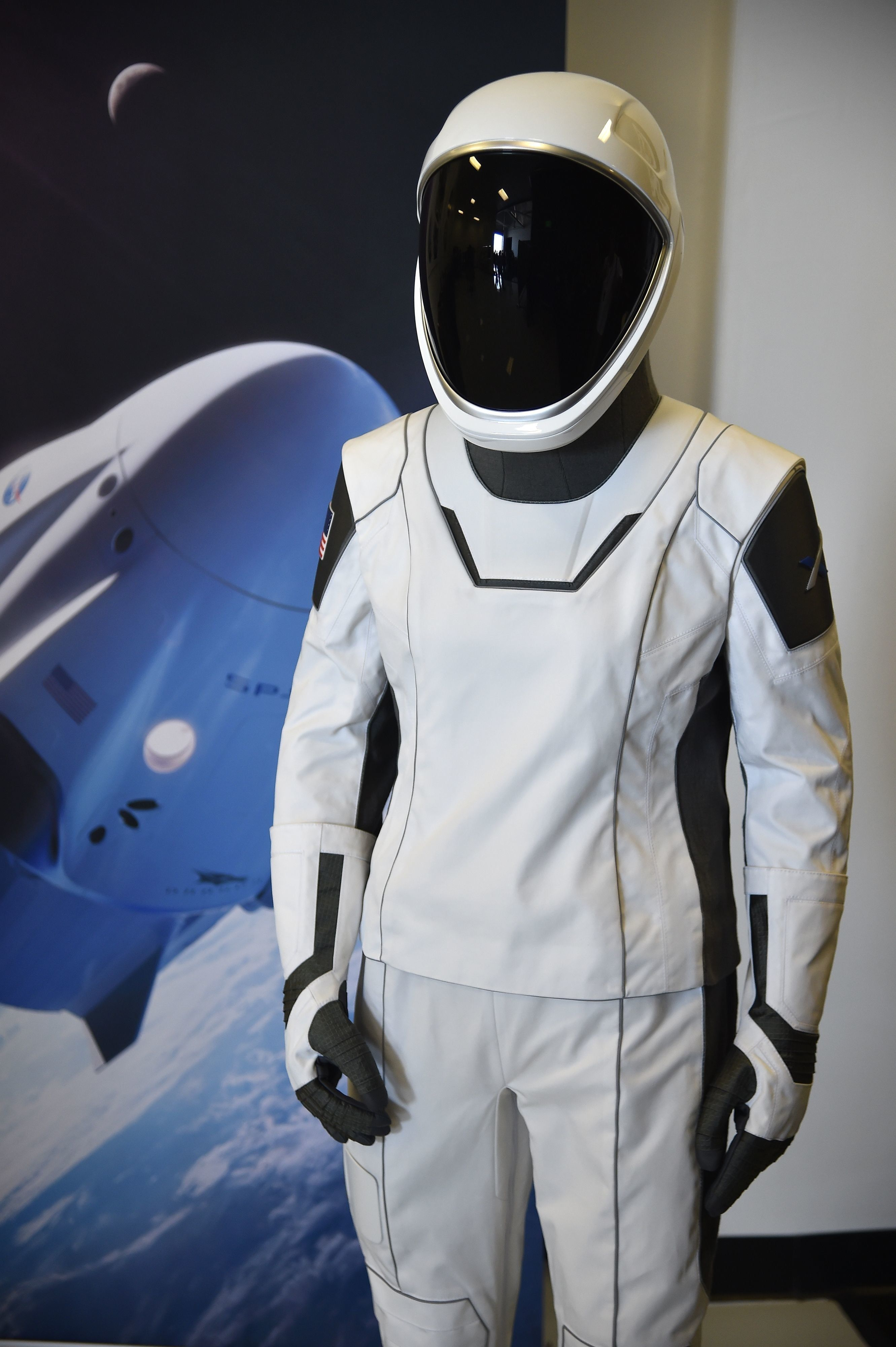 The SpaceX spacesuit to be wore by NASA astronauts that will travel to the International Space Station aboard the SpaceX Crew Dragon capsule is displayed during a media tour at SpaceX headquarters in Hawthorne, California, on August 13, 2018. - According to the Teslarati website the majority of the helmet is 3D printed and SpaceX has used that capability to directly integrate valves, a number of complex mechanisms for visor retraction and locking, microphones, and even air cooling channels into the helmets structure. The suit itself is designed so that necessary external connections (power, water, air, etc) all pass through one single umbilical panel located in the middle of the suitÕs right thigh.  The suit is designed to allow astronauts to work in extreme conditions including hard vacuum but not space walks. (Photo by Robyn Beck / AFP)        (Photo credit should read ROBYN BECK/AFP/Getty Images)