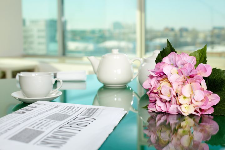 Table with porcelain cup and pot, newspaper and bunch of flowers on it