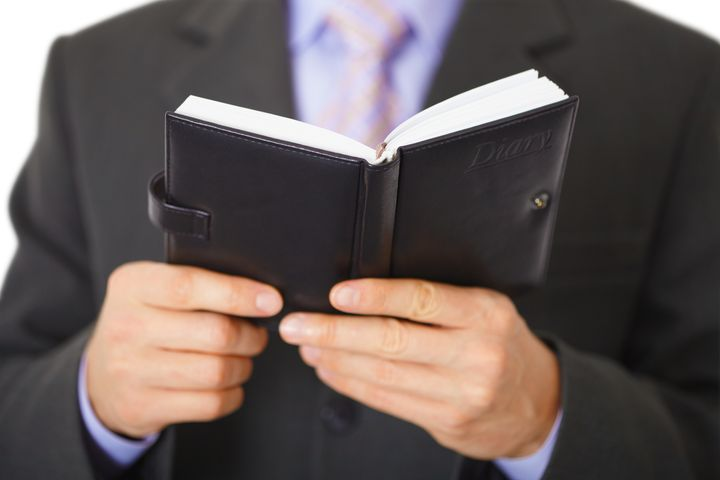 Businessman reading a small notebook with the inscription - Diary