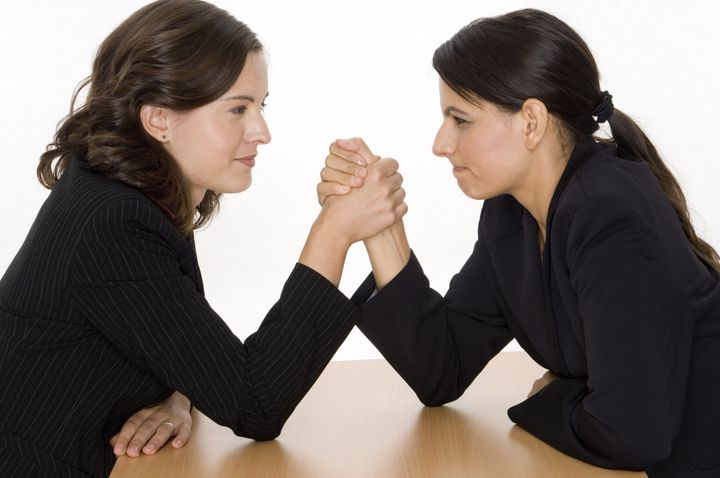 two women arm wrestling at work ...