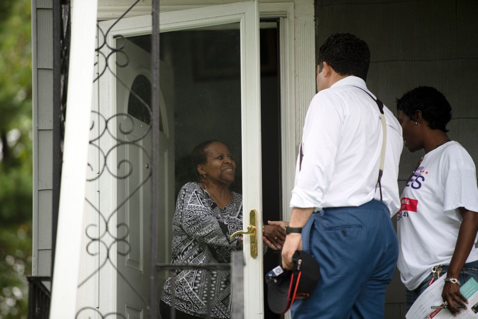 Ben Jealous chats with a voter while canvassing in Baltimore.