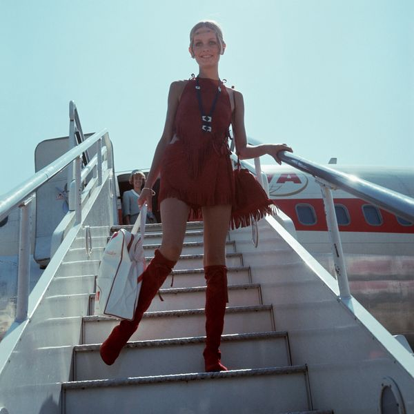 Twiggy disembarks from an aircraft in a red suede velvet outfit.