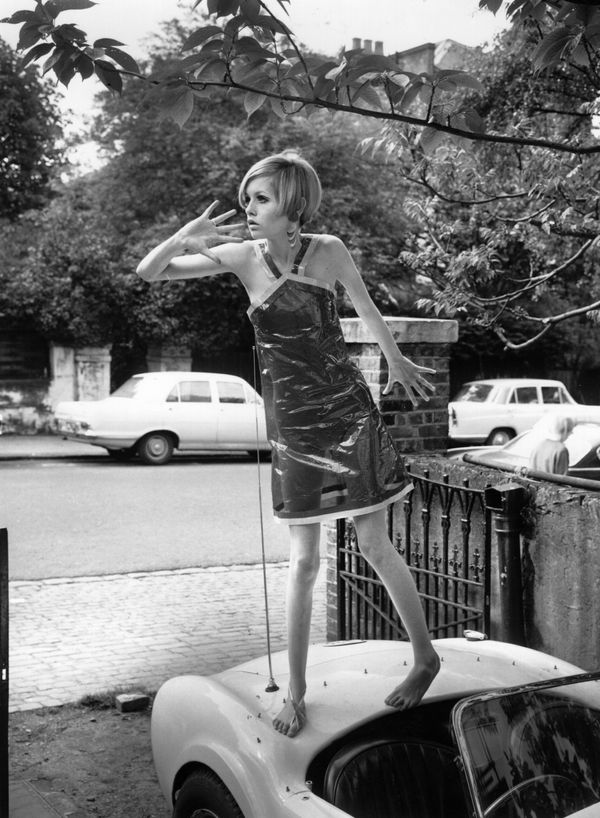 Twiggy models a transparent plastic halter neck dress while standing on a car.