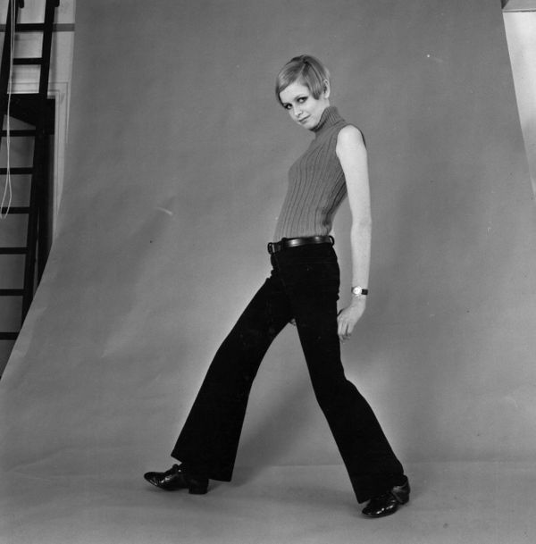 Twiggy models flared trousers and a sleeveless top in a photographer's studio.