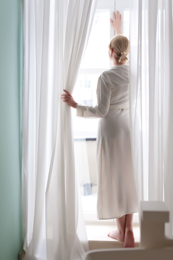 Beautiful blonde young woman, silk bathrobe, standing by the window, between the curtains,  natural light