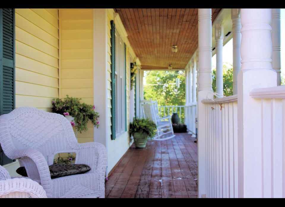 White wicker chairs brighten up this rustic porch.