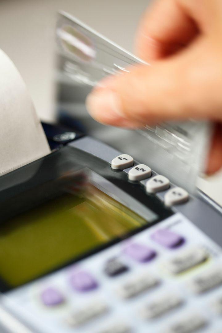Close up of hand swiping credit card