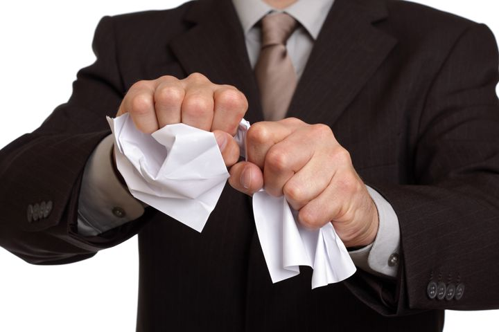 angry businessman tearing up a...