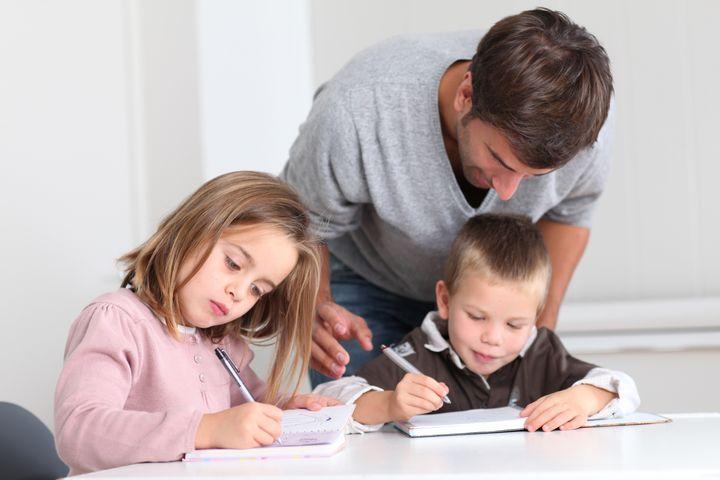 Man helping kids with homework