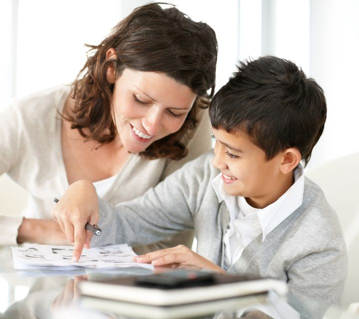 Portrait of a sweet mature woman and boy reading a book together