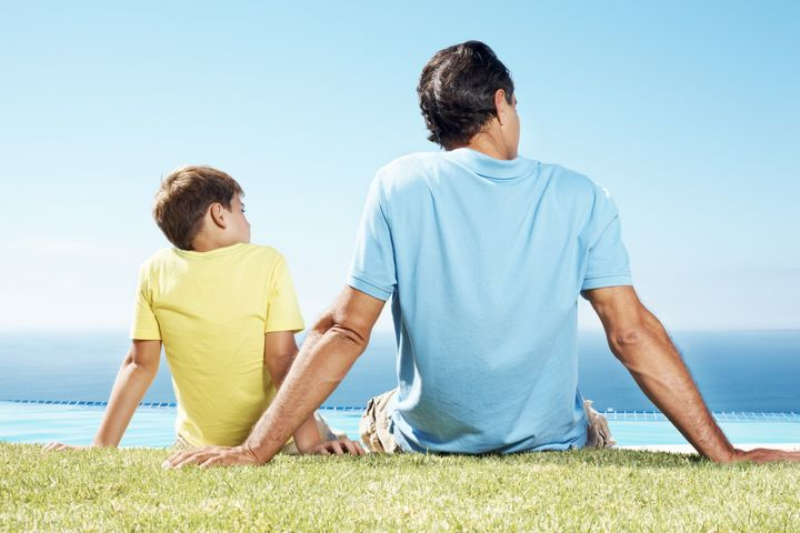 Father and little son sitting on grass and looking at scene - Rear view