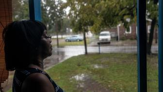 Shirley Griffin, 65, watches the floodwaters from her front porch. The water reached the curb in front of her home early Friday morning before it began to slowly recede.
