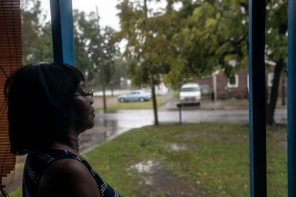 Shirley Griffin, 65, watches the floodwaters from her front porch. The water reached the curb in front of her home early Frid