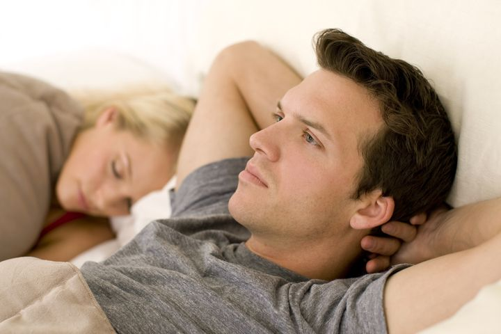 Couple in bed, man looking worried