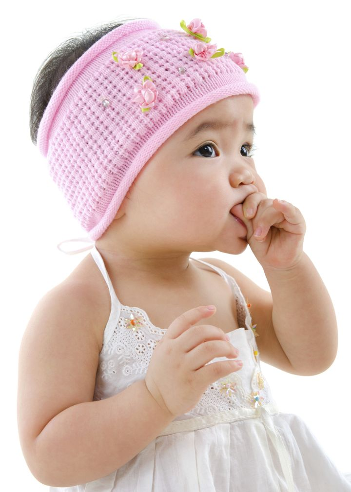 Cute pan Asian baby girl eating on white background